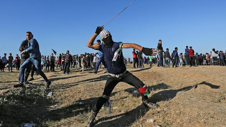 En protesterande palestinier kastar sten mot israeliska soldater vid fortsatta oroligheter vid Gazas gräns mot Israel.