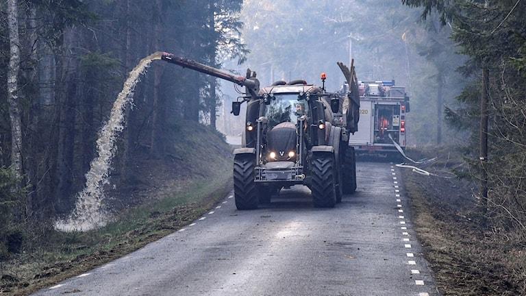 Traktor med gödseltank sprutar vatten utmed en väg i skånska Hästveda på tisdagskvällen.