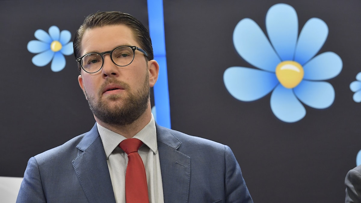 Bild på man i mörk kostym och rostfärgad slips. Han står framför banderoll med blommor.