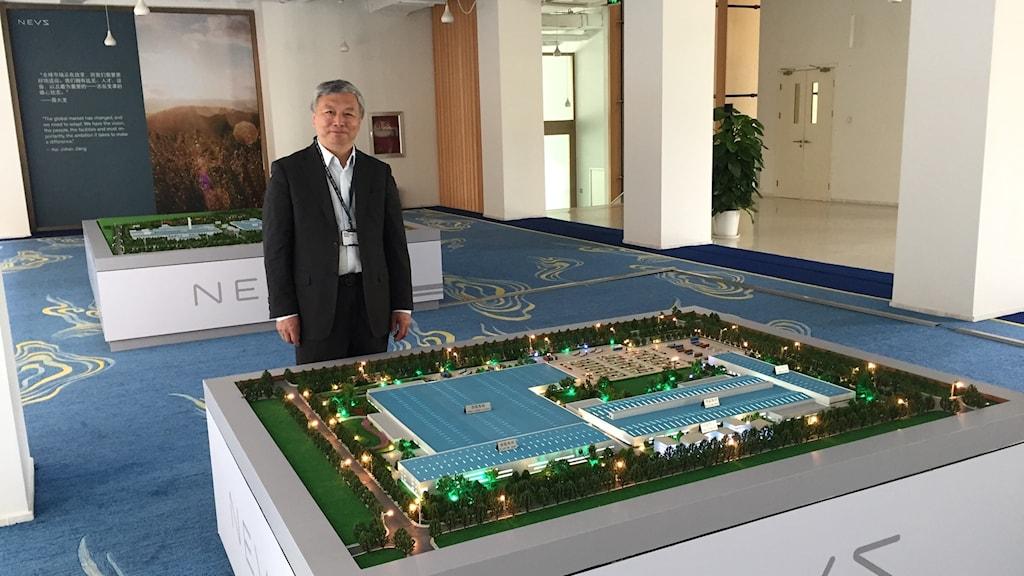 Nevs huvudägare Kai Johan Jiang framför en modell av fabriken som byggs i Tianjin