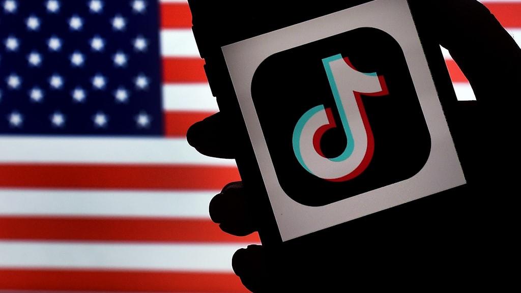 Tiktok logotypen i förgrunden. USA:s flagga i bakgrunden.