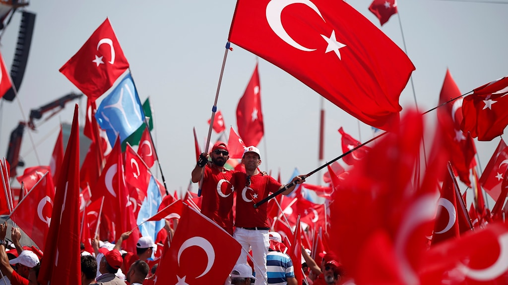 Folk viftar med den turkiska flaggan i rött.