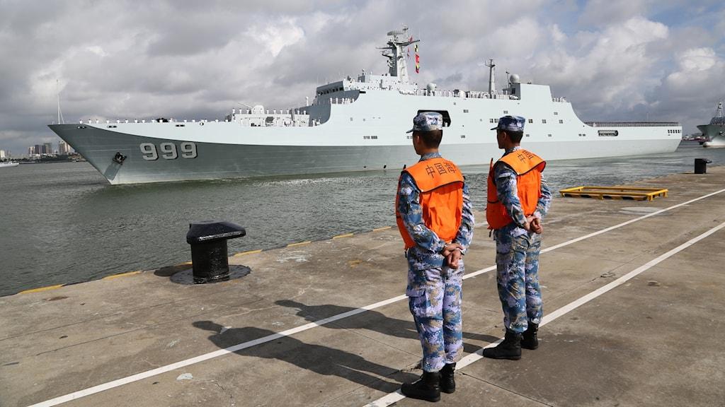 Två män framför en stor militärbåt.
