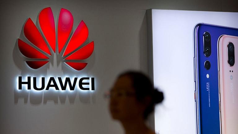 Kvinna går förbi en Huawei-logga.