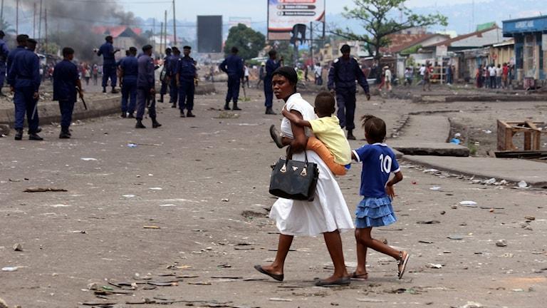 En kvinna med barn går förbi beväpnade män.