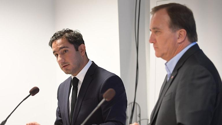 Två män står framför varsin mikrofon.