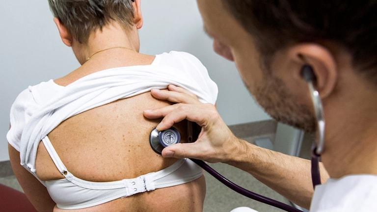 Läkare lyssnar med stetoskop på patient.