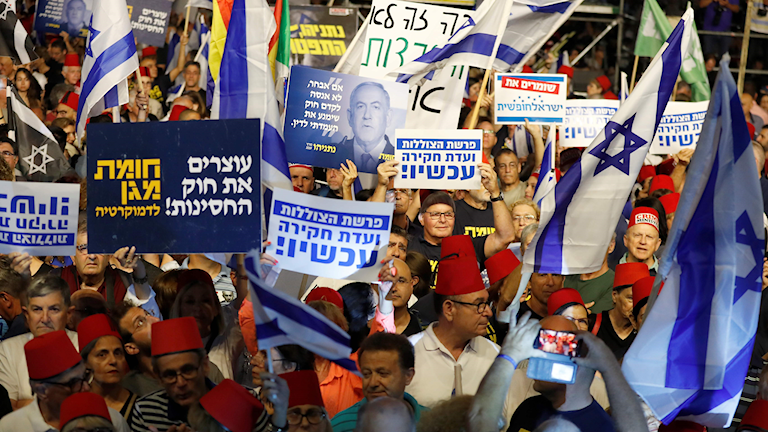 Demonstranter med flaggor och plakat i Tel Aviv