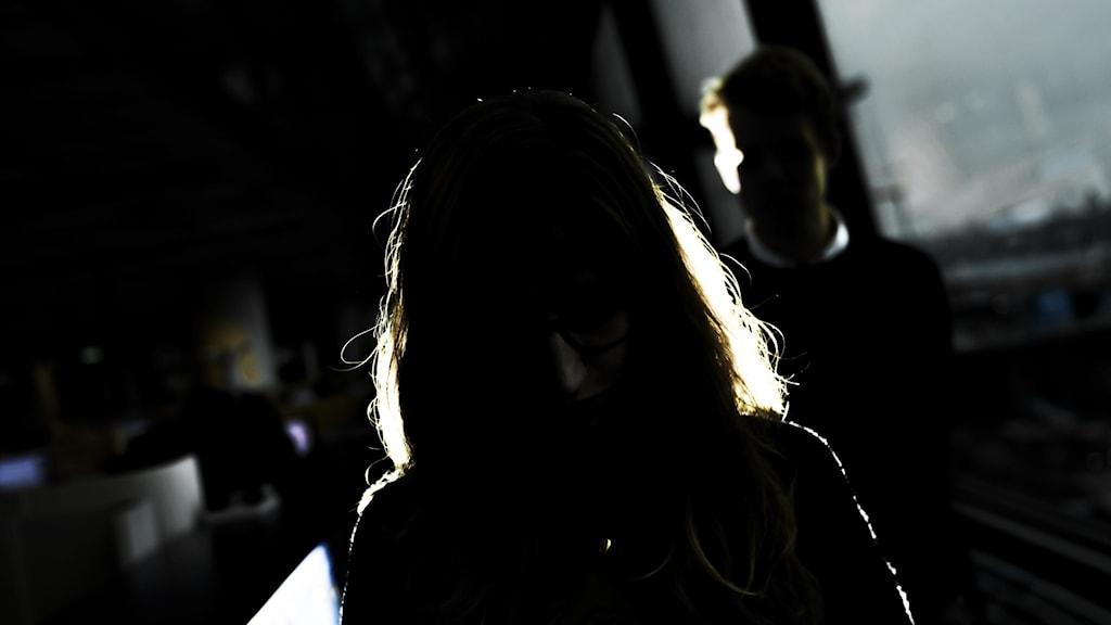 En kvinnas silhuett syns i ett mörkt rum.