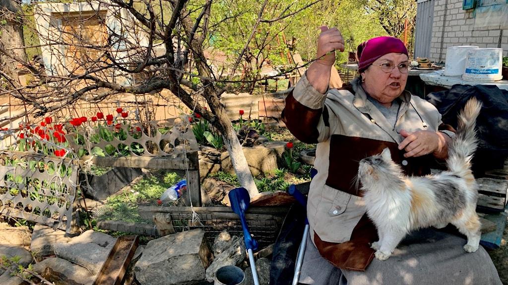 Vera Ivanovna sitter utanför sitt hus i byn Luhanske när granater slår ner långt bort i fjärren.