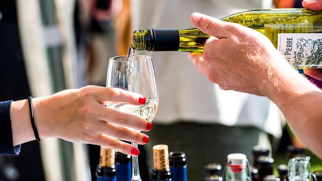 En bartender häller upp vin i ett glas som en kvinna håller i.