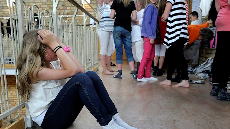 tjej sitter och håller upp armarna för ansiktet, ledsen, flera andra elever står i grupp en bit bort.