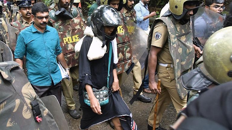 Kvinna eskorteras av poliser på sin väg till templet.