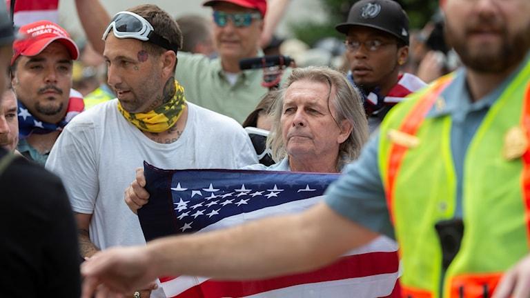 Två personer med en amerikansk flagga.