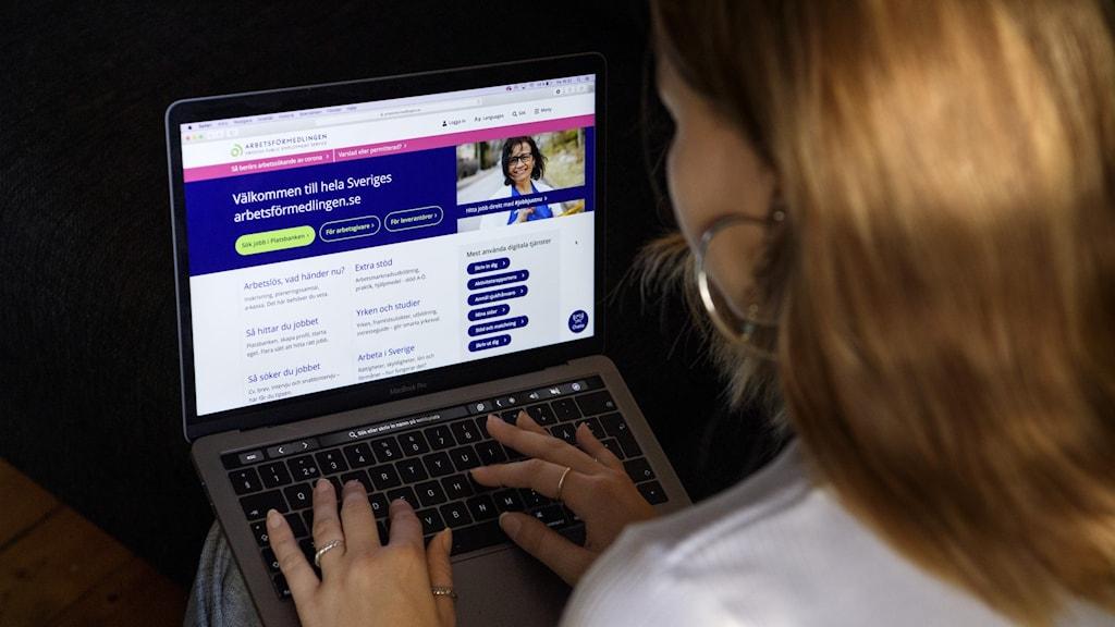 Ung kvinna framför dator