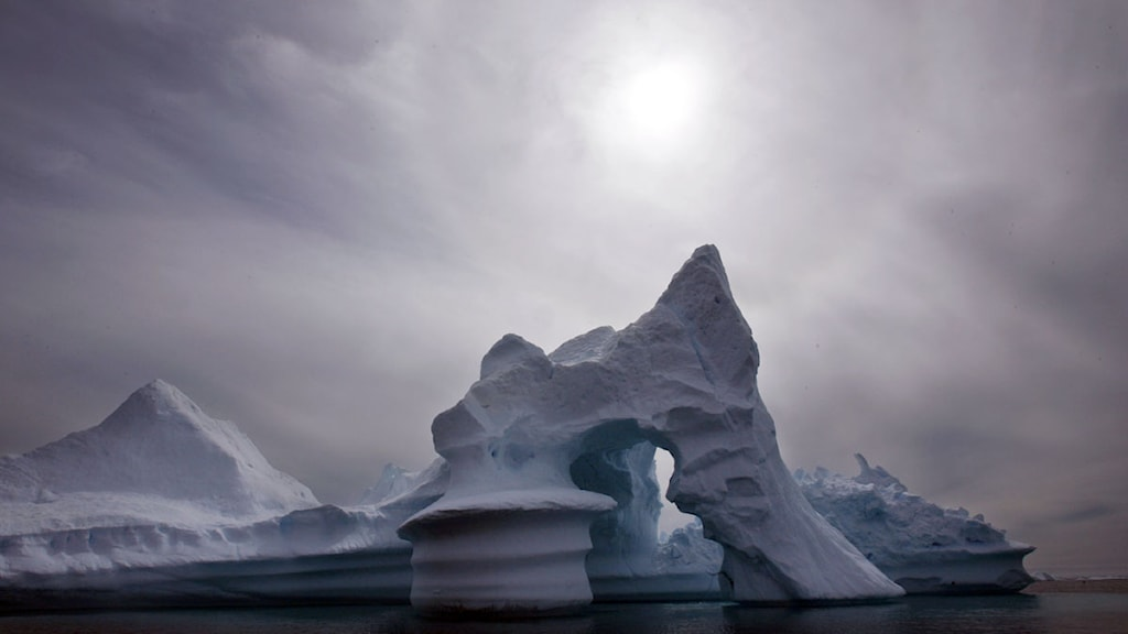 Isberg i havet framför soldisig himmel. Foto: John McConnico/Scanpix.