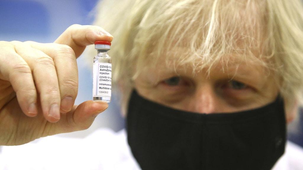 Boris Johnson håller en dos Astra Zeneca-vaccin.