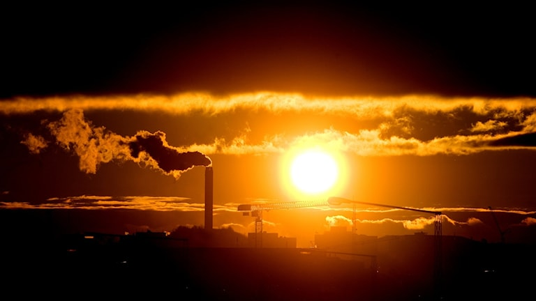 Fabriksutsläpp i solnedgång .