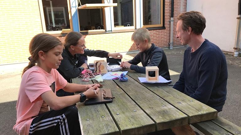 Elever och lärare sitter vid ett bord och virkar.