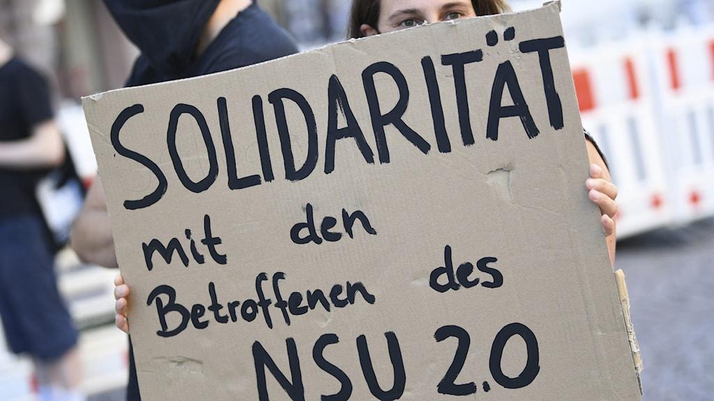En person som vill visa solidaritet med offren för en neonazistisk grupp demonstrerar i Wiesbaden i Tyskland. Arkivbild