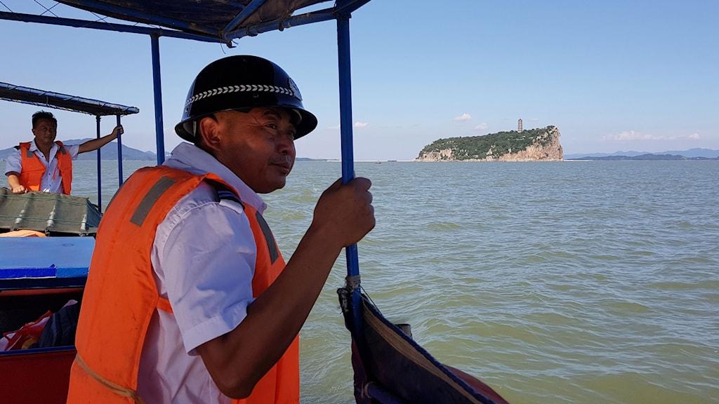 två män med flytväst på båt