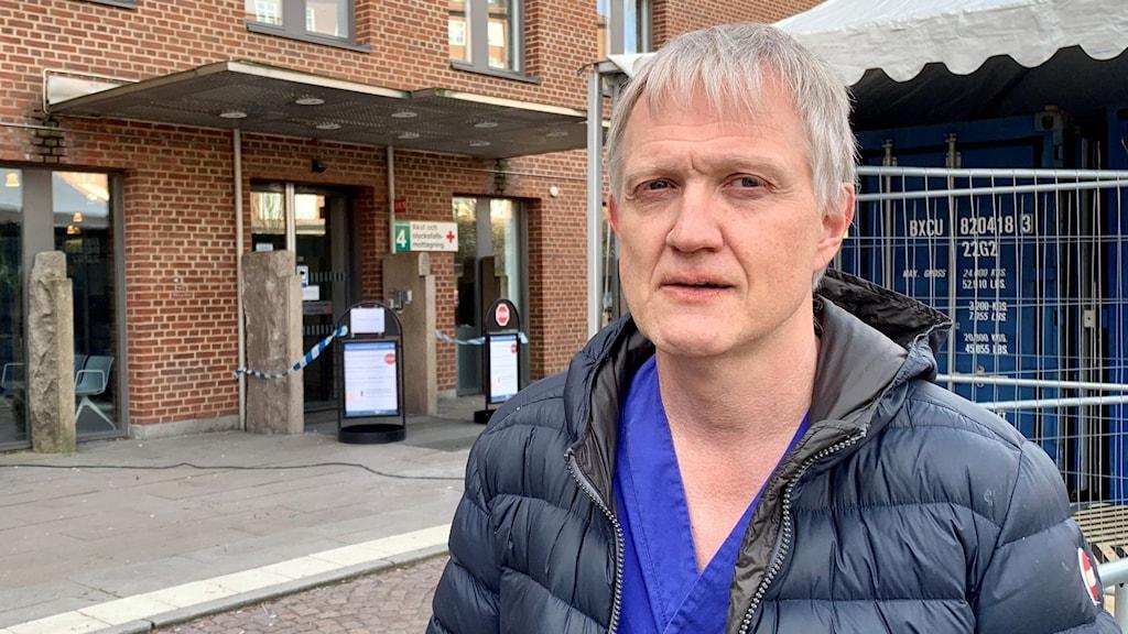 Bild på en läkare. Han ser ut att stå utanför sjukhuset. I bakgrunden skymtar man ett tälttak med en blå container i.