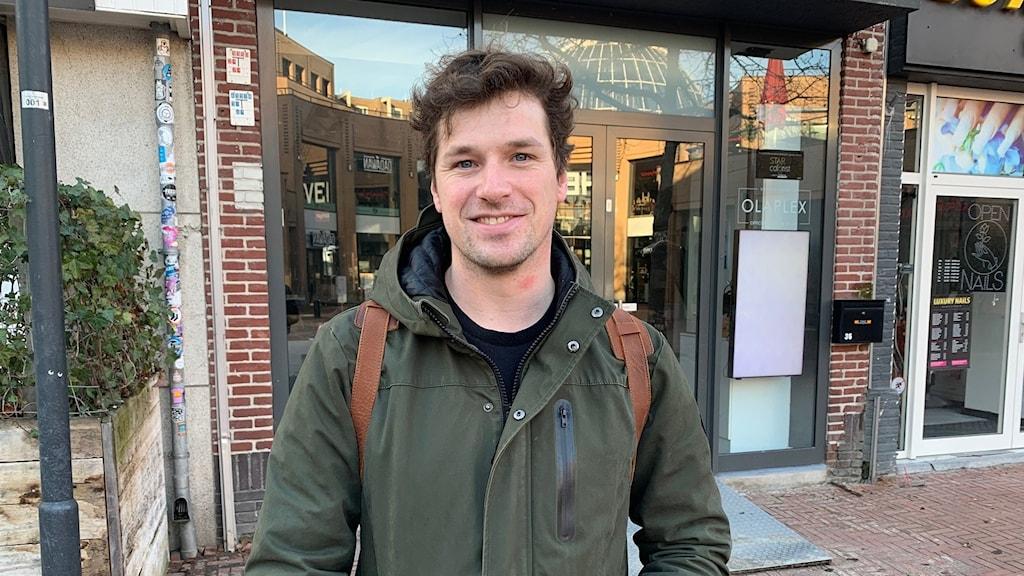 En man i höstjacka framför en affär i Holland.