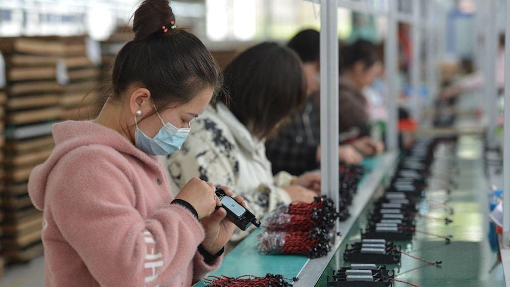 Anställda i en fabrik arbetar med att montera högtalare.