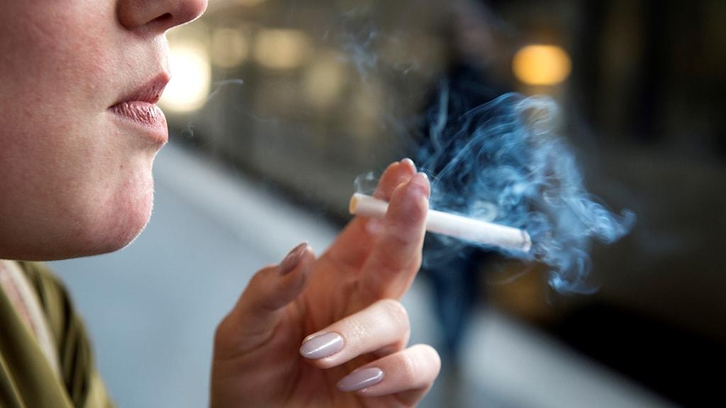 Kvinna som blåser ut rök från en cigarett