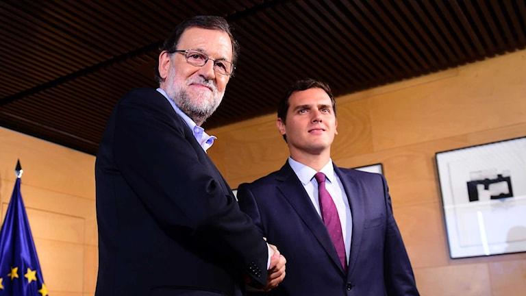 Sittande premiärministern Mariano Rajoy och Ciudadanos-ledaren Albert Rivera skakar hand.