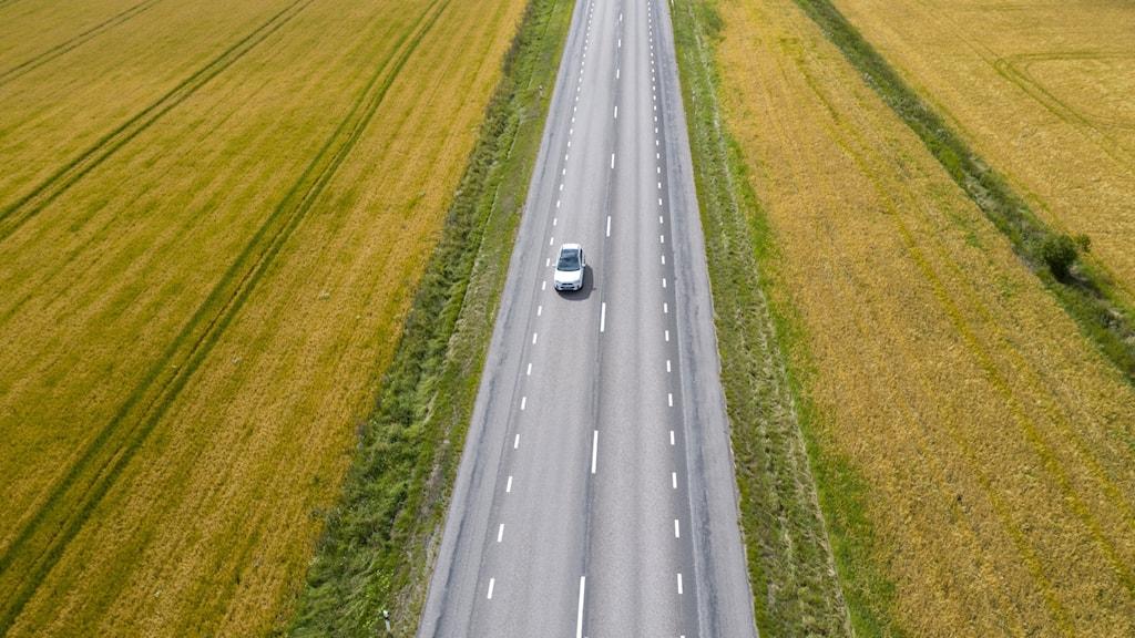 En bil på en väg i öppet landskap
