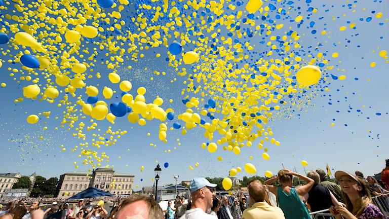 Gula och blå ballonger släpps upp i luften vid Skeppsbron i centrala Stockholm.