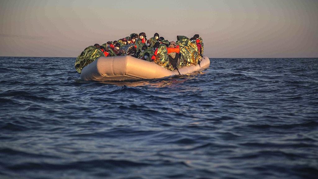 Migranter från olika länder färdas på en överfull gummibåt över medelhavet mot Spaniens kust.