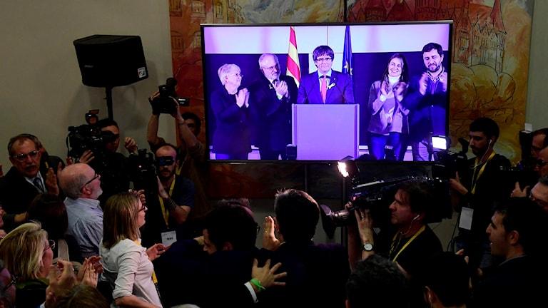 Carles Puigdemont talar för sina anhängare via video-länk.