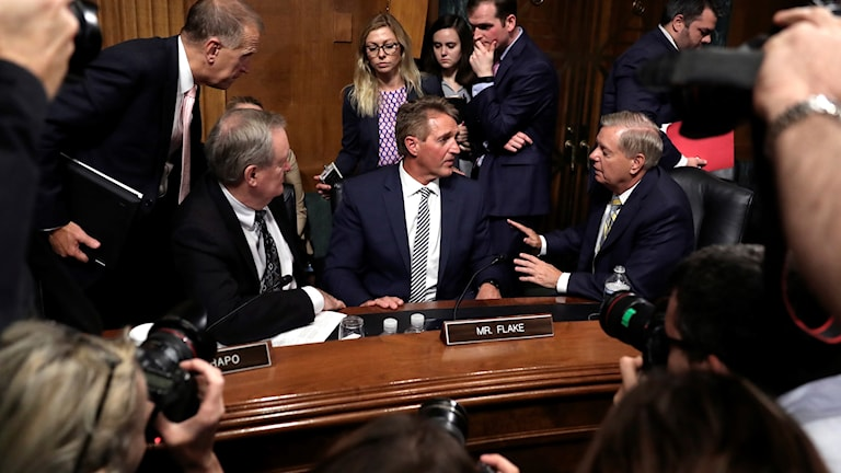 Den republikanske senatorn Jeff Flake i mitten i diskussioner med andra senatorer under justitieutskottets möte.