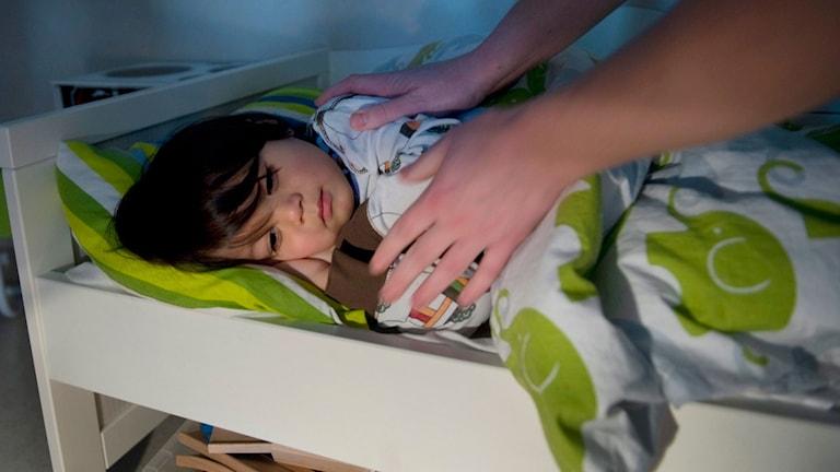 Ett barn ligger i en säng och nattas av en förälder.