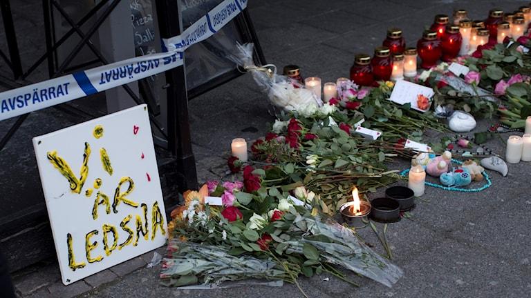 Blommor och ljus vid platsen för skottlossning i Biskopsgården