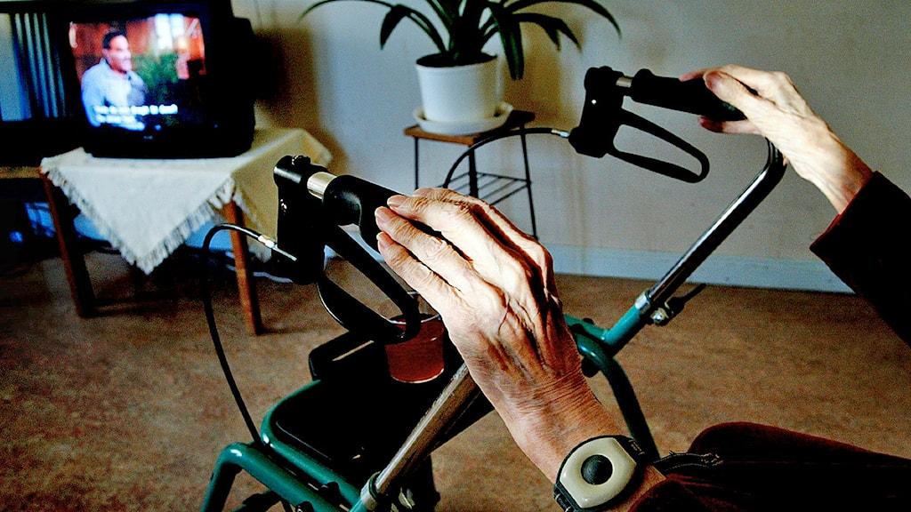En äldre kvinna med rullator sitter och tittar på tv på ett äldreboende.