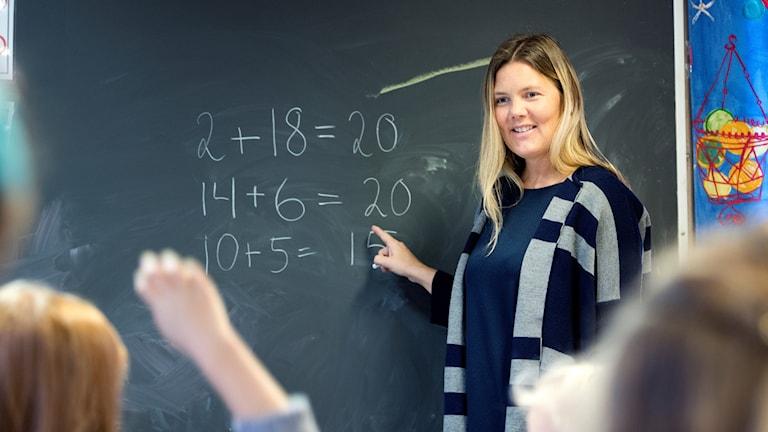 Lärare pekar på ett mattetal på en svart tavla