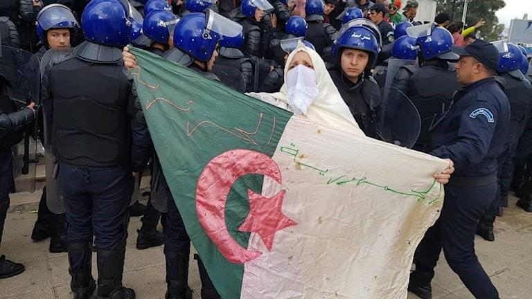 Kvinna som håller upp Algeriets flagga framför kravallpoliser.
