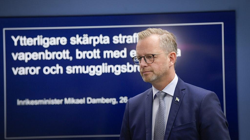 """Inrikesminister Mikael Damberg framför en skärm med texten """"skärpta straff"""" för bland annat vapenbrott."""