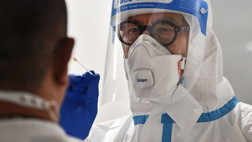 Man i visir och mask håller fram en bomullspinne under provtagning för coronaviruset.