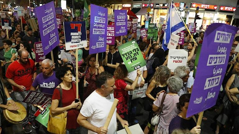 Demonstranter håller upp skyltar.