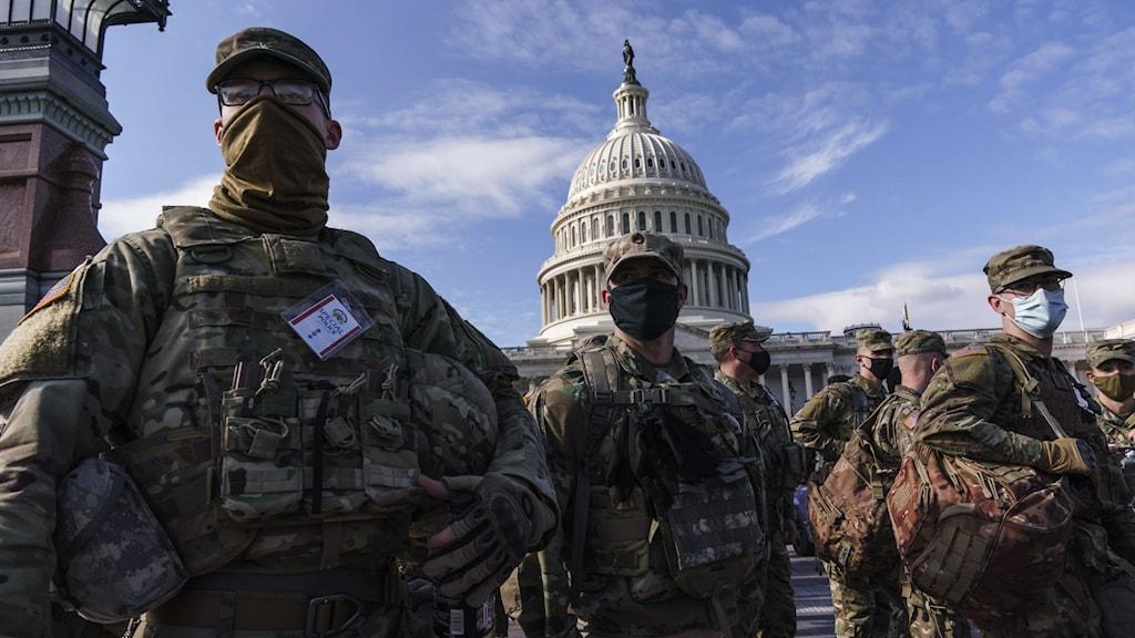 Män står upp iklädda militärkläder.