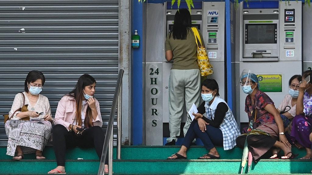 Personer i myanmar som väntar vid en bankomat.