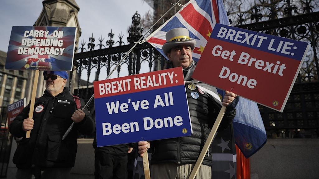 """Män med skyltar med budskapet """"få brexit avklarat."""""""