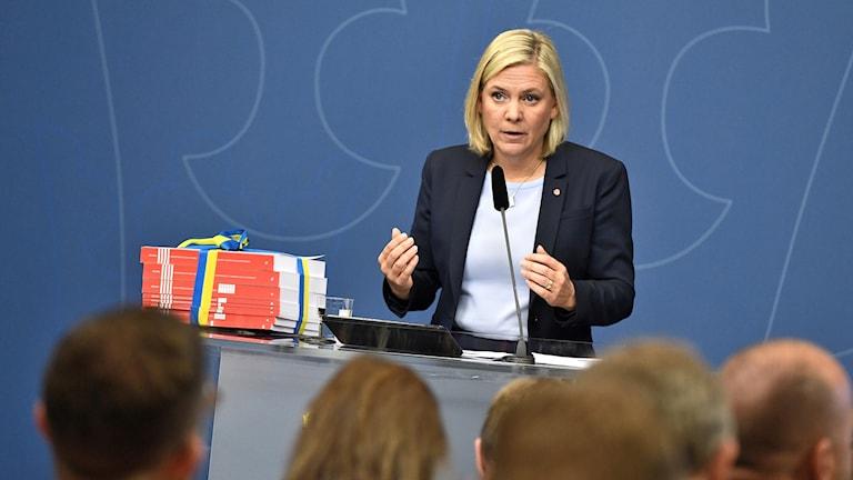 Kvinna med mikrofon framför människor.