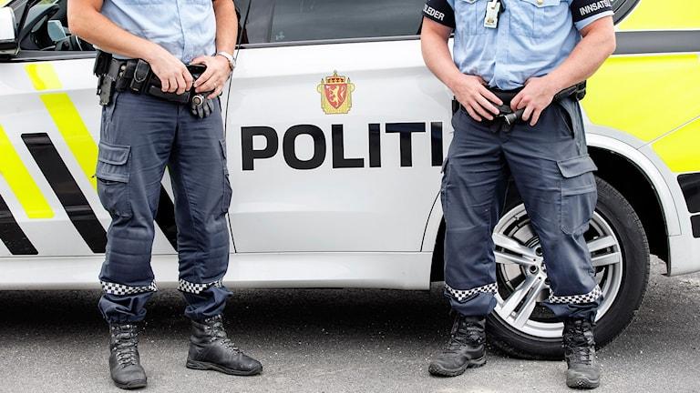 Två norska poliser framför en polisbil.
