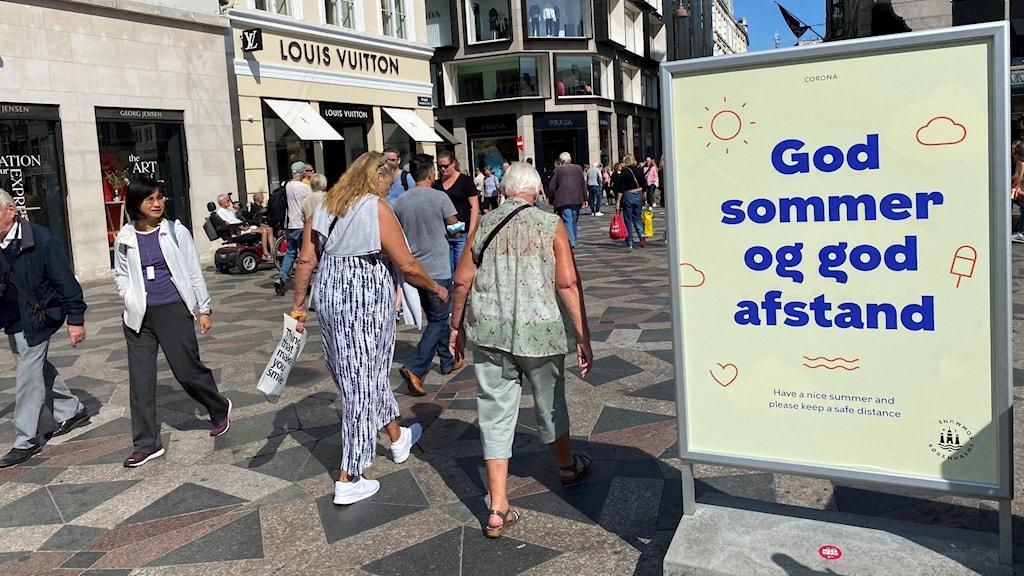 Folk går på en gata, och en skylt bredvid upplyser om att man ska hålla avstånd. Foto: Petra Haupt/Sveriges Radio
