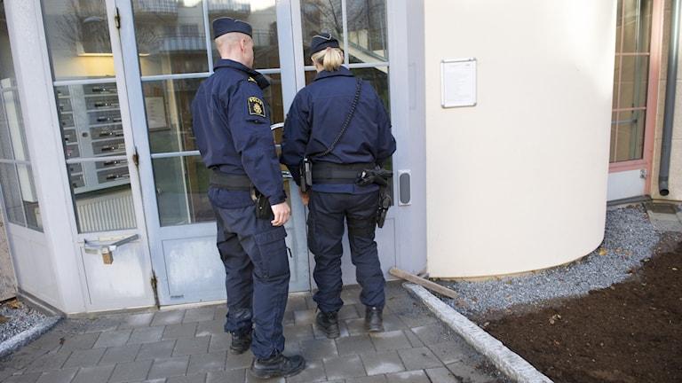 En kvinnlig och en manlig polis tar sig in i ett flervåningshus under sin yttre tjänst.